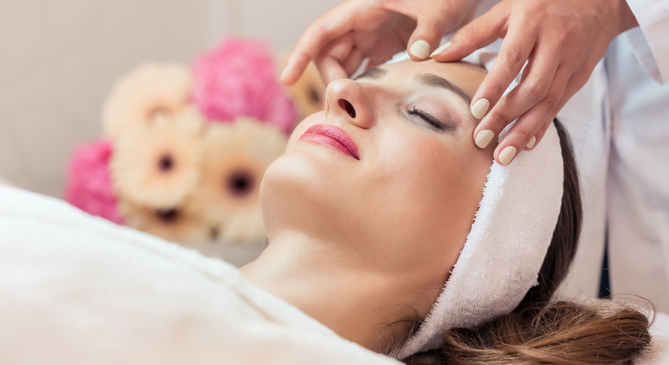 Beautiful woman relaxing during rejuvenating facial massage in a
